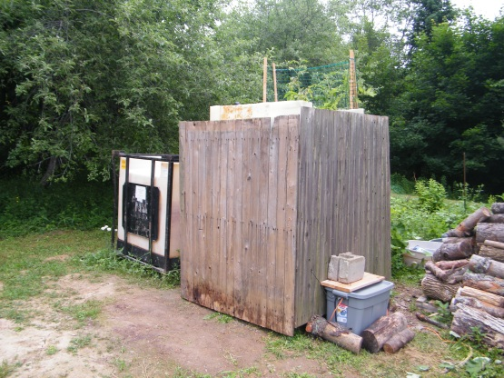 Our newly fenced aquaponics system, with the electronics box in the lower right and a raw IBC on the left.